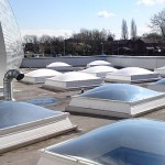 Before and after Solar Reflective Paint applied to rooflights.Ones in foreground untreated.